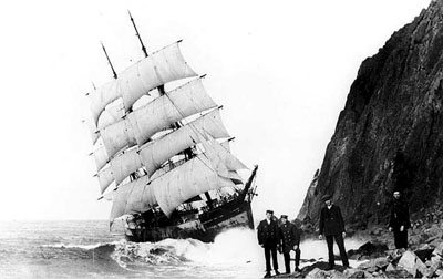 Under almost full sail, the doomed Glenesslin grinds against the side of Neahkahnie Mountain as its crew members pose for the camera.