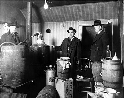 Law enforcement officers raiding an indoor moonshine still in King County, Washington.