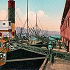 This postcard picture from the 1910s shows a steamer at a dock in Portland being loaded with wheat using conveyer belts. The men tending the belts, loading and unloading 200-plus-pound sacks of wheat, are longshoremen.