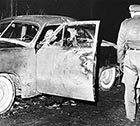 Investigators look over Larry Peyton's car after his body has been removed, on Sunday, Nov. 27, 1960.
